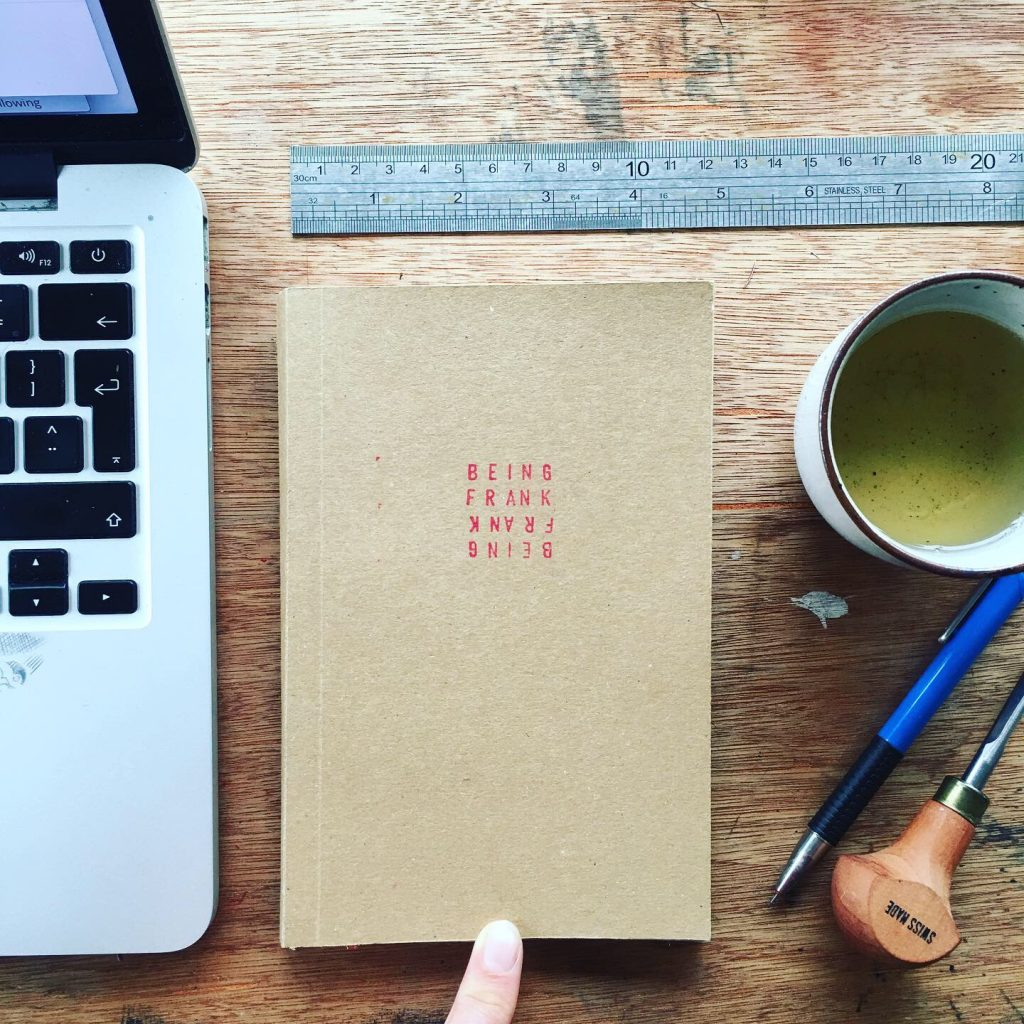 image of cover of Being Frank book by south Wales illustrator Frank Duffy, with macbook, ruler, pencil, pfeil lino tool and cup of tea