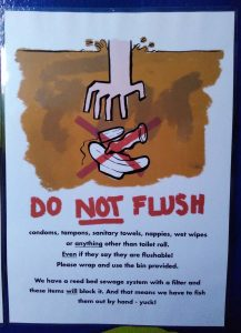 a sign showing a hand descending into sewage to pull out a tampon, a condom and a sanitary towel, all with a big red cross over them. Underneath the image is a list of what mustn't be flushed at Beech Hill